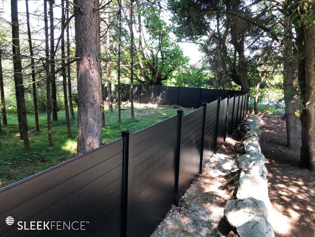 Aluminum privacy fence beside rock wall