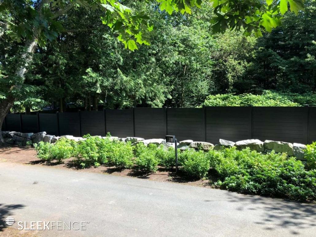 Black fence beside greenery