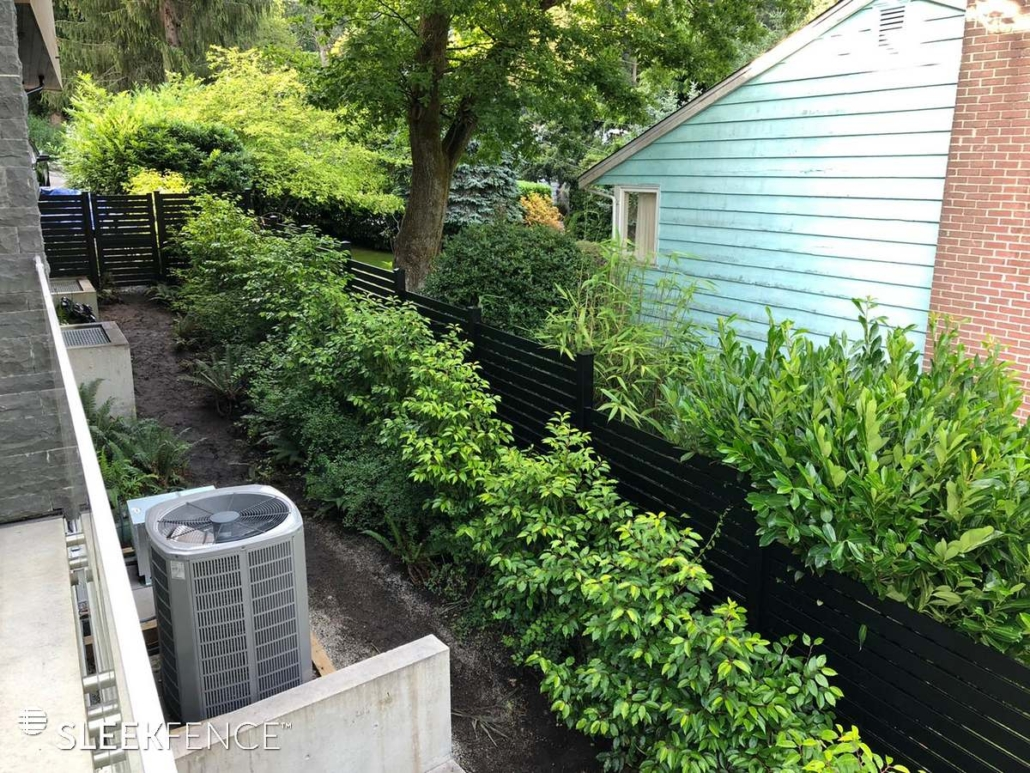 Black fence with beautiful green hedge